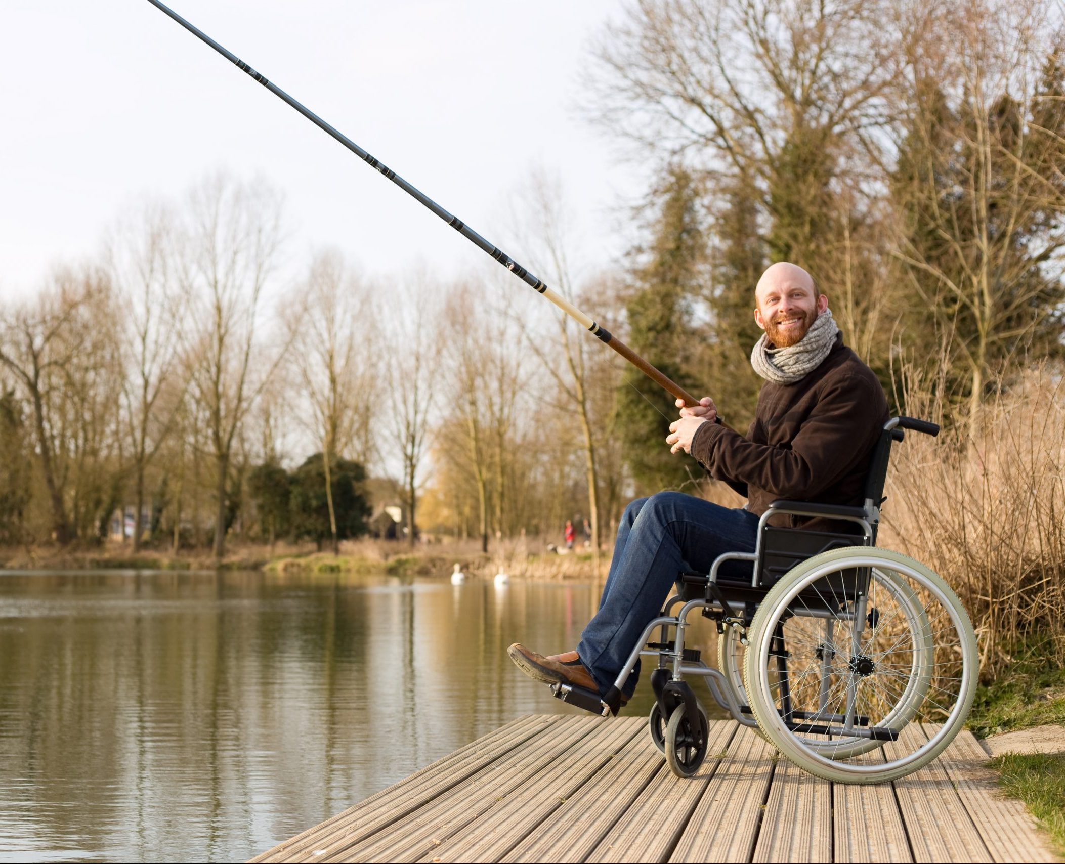 A man in a wheelchair enjoying fishing on the side of a lake