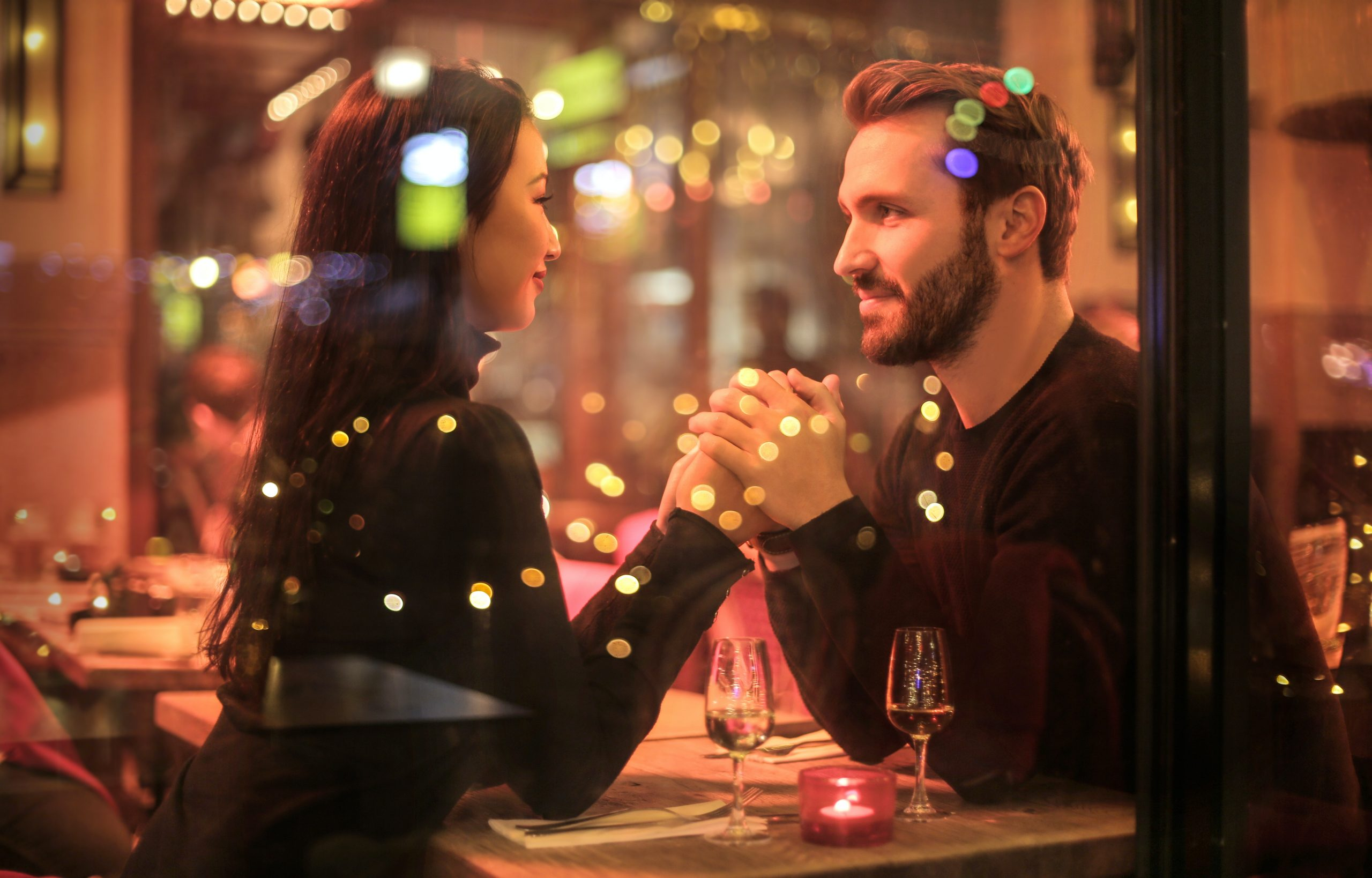 A man and a woman hold hands looking at each other at a restaurant
