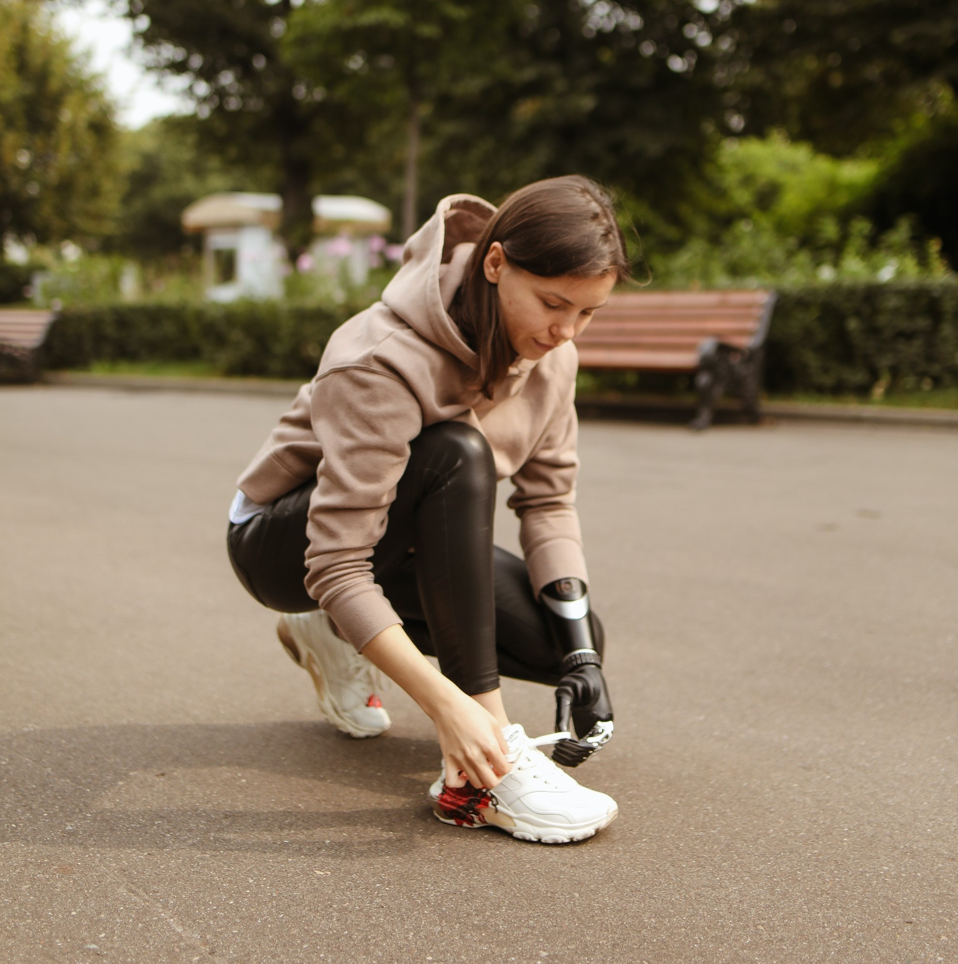 A woman bends down to tie her shoe