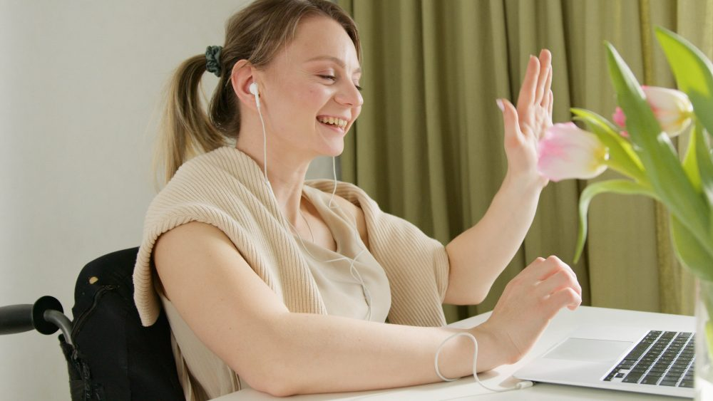 woman in wheelchair, sitting at a desk, wearing headphones, waving to her computer, talking to someone on a video call