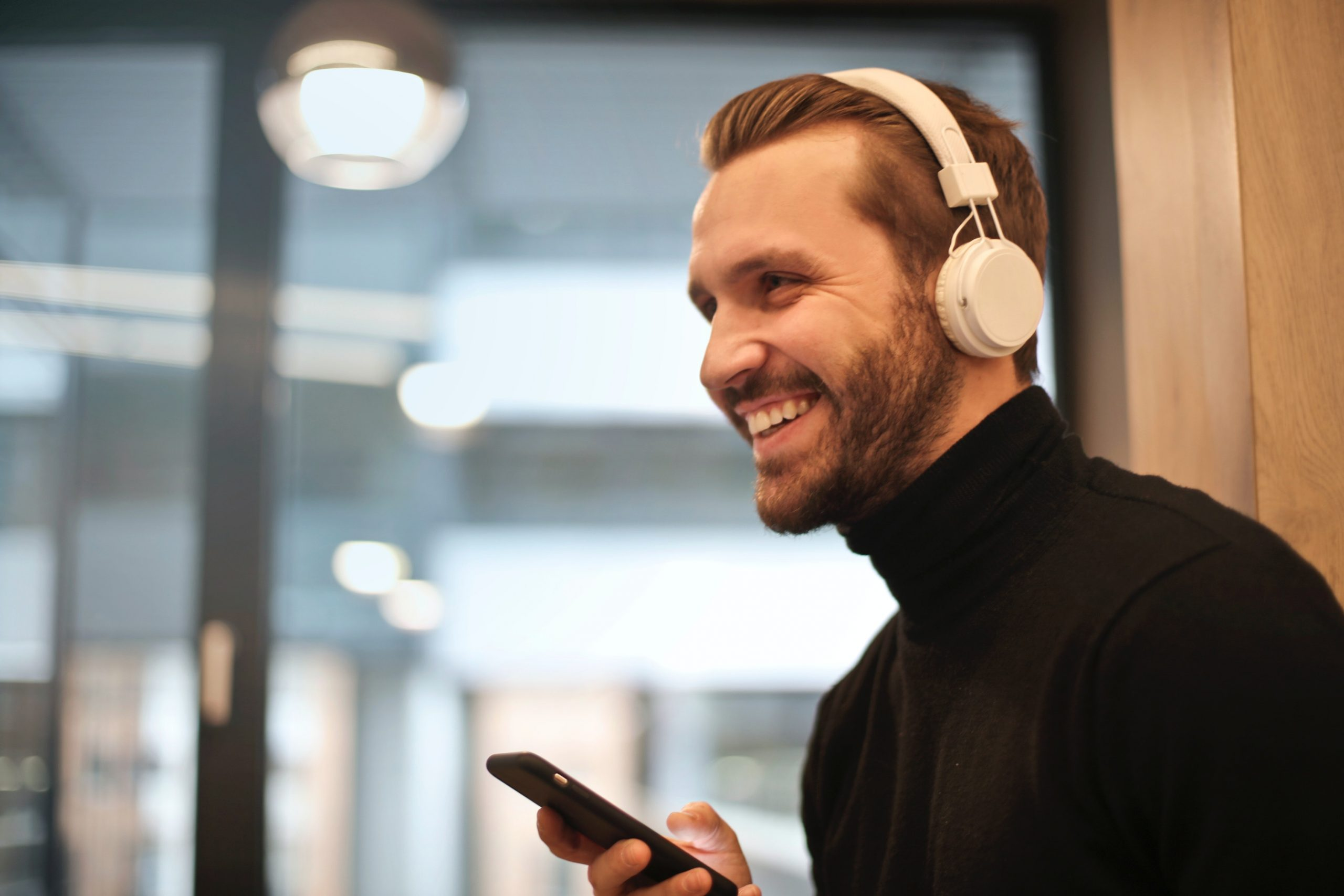 man with beard and black top, smiling, with white headphones on and holding a smartphone.